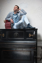student sits on an upright piano with books