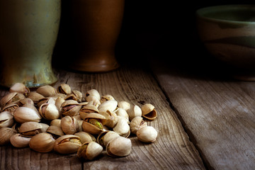 pistachio nuts on dark wood, copy space in the background