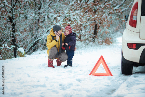 woman with a child on the winter road - 76126652