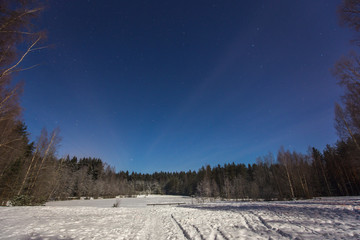 Frozen winter lake in magic moonlight at night