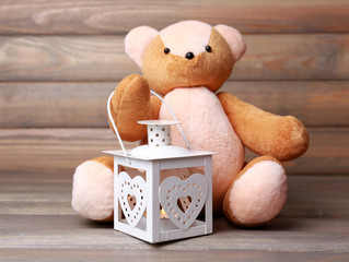 Teddy Bear with lantern on wooden background