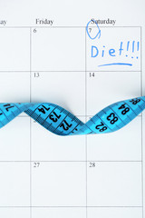Diet concept - measure tape on calendar, close up