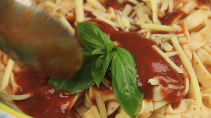 Pasta sauce being poured on fresh basil on pasta.