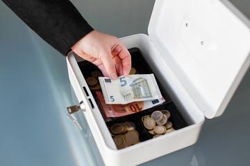 Businesswoman put five euro into safe box