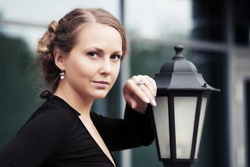 Beautiful fashion woman standing at lamppost