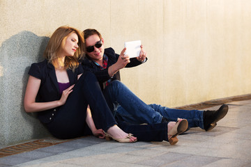 Young fashion couple with tablet computer sitting at the wall