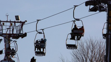 Chairlift with people moves upwards mountain in the city