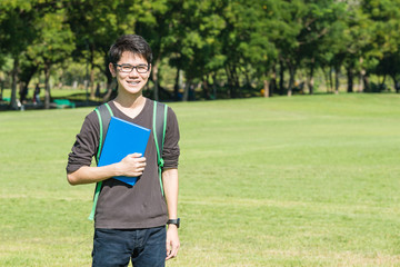 Asian student holding books and smiling while standing in park a