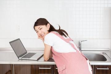 パソコンを見ながら料理をする女性