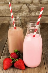 Strawberry and chocolate milk in bottles on old wood