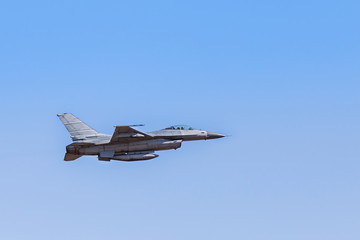 f16 falcon fighter jet on blue sky background