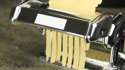Fettuccine pasta coming out of pasta machine