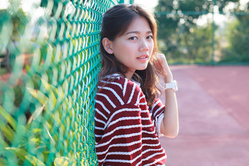 portrait of beautiful young teen woman leaning steel net fence a