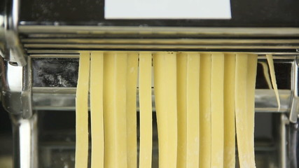 Fresh fettuccini pasta coming out of pasta machine