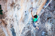 Rock climber holding on handhold while climbing cliff