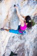 Young female rock climber gripping handhold while lead climbing