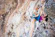 Young female rock climber looking up while lead climbing