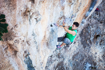 Young male rock climber struggling to make on his way up