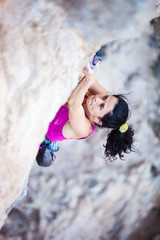 Young female rock climber clipping rope while lead climbing
