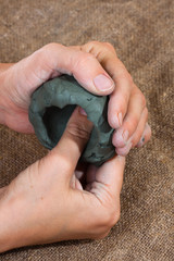hands molded from clay a cup