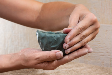 women's hands molded from clay a tea bowl