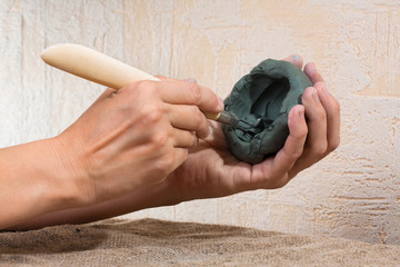 women's hands working with blue clay