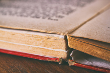 Open old book over wooden table. macro image with selective focu