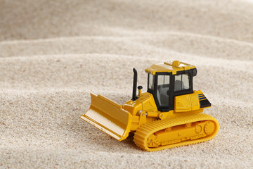 Heavy crawler toy bulldozer on sand dune