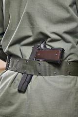 Soldier in uniform and gun on his belt