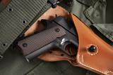Colt pistol in holster and belt lie on military jacket