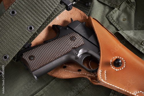 Leinwanddruck Bild Colt pistol in holster and belt lie on military jacket