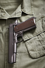 Colt pistol lie on military jacket