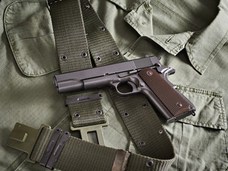 Colt gun pistol and belt lie on military jacket