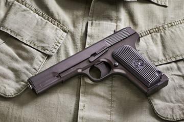 TT russian pistol and belt lie on military jacket