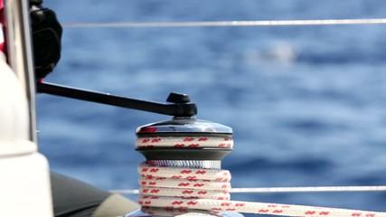 Man pulling ropes, winding sheets around winches. Sailing.
