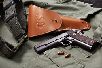 Colt gun pistol, holster and belt lie on military jacket