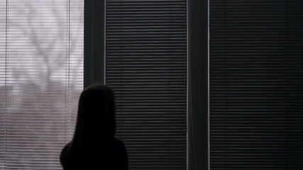 Girl opens a window blinds