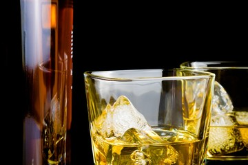 whiskey with ice in glasses in front of bottle