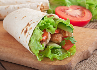Fresh tortilla wraps with chicken nuggets and vegetables on plat