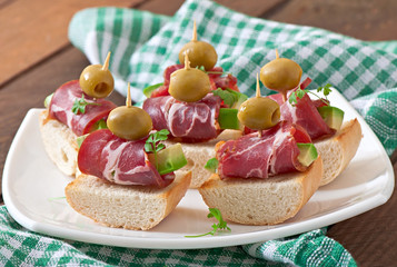 Snack on toast with ham, avocado and olives