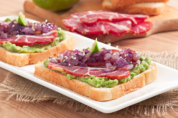 Sandwich with ham, avocado sauce and caramelized onions
