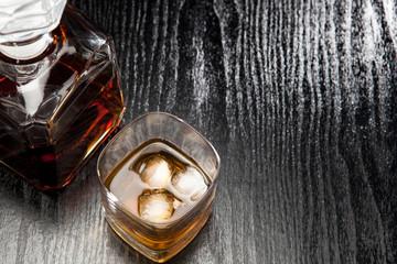 Alkohol im Glas mit Eiswürfeln und Karaffe daneben