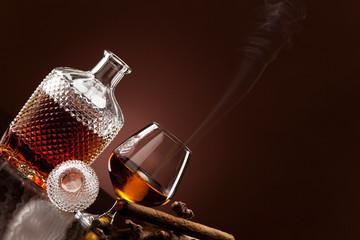 Ein edler Tropfen Alkohol und eine rauchende Zigarre