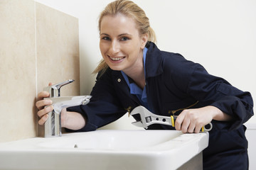 Female Plumber Working On Sink Using Wrench