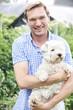 Portrait Of Man With Pet Dog In Garden