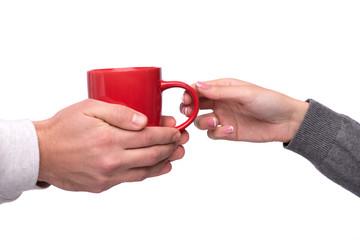 Hand passing a mug of coffee