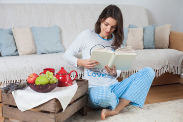 Young attractive woman, reading a book at home, eating fruits