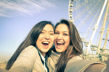 Young women girlfriends taking a selfie at luna park