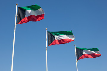 Three national flags of Kuwait waving in the wind