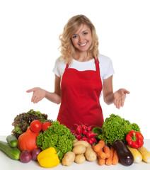 Hausfrau mit roter Schürze präsentiert frisches Gemüse